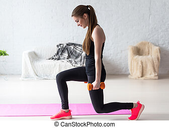 Athletic woman warming up doing weighted lunges with...