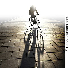 Back lit cyclist in evening light casting long shadow on...