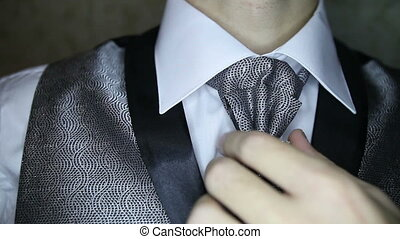 groom corrects brooch on dark silver necktie - groom in dark...
