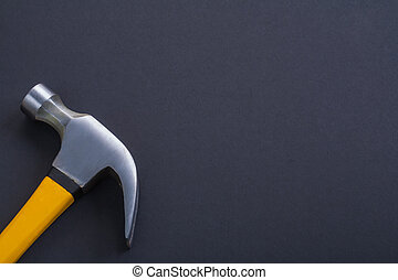 claw hammer with yellow handle on black background