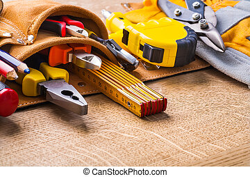 construction tools in toobelt very close up on wooden board