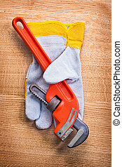 monkey wrench protective work glove on wooden board...