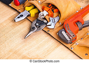 toolbelt with tools on wooden board