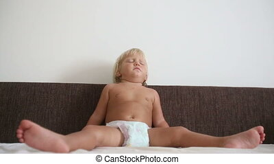 blonde little girl sleeps in twine pose on sofa at home