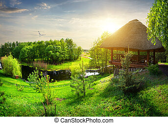 Wooden arbour with thatched roof near river