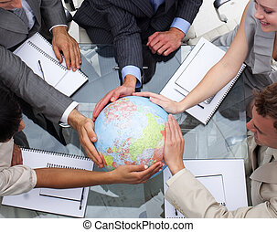 High angle of business team holding a terrestrial globe....