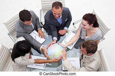 High angle of business people holding the world. Worldwide...