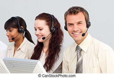 Smiling young businessman working in a call center