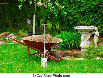 Wheelbarrow Full of Dirt with Leaning Shovel in Garden - A...