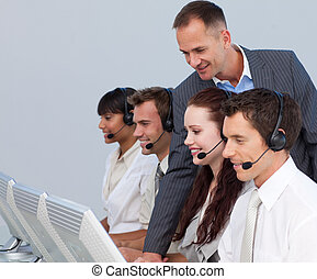 Attractive manager checking his team work in a call center -...