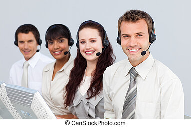 Smiling people with a headset on working in a call center -...