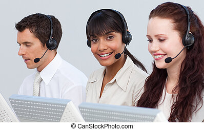 Young team with a headset on working in a call center and...