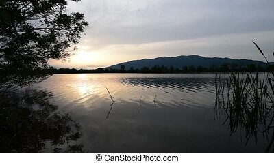 Sunset on mountain lake - Mountain lake with sounds of...