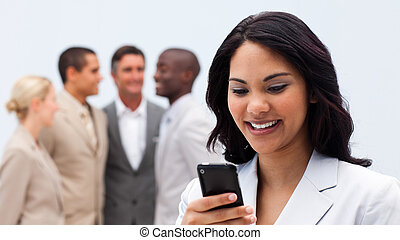 Smiling ethnic businesswoman sending a text with her team in...