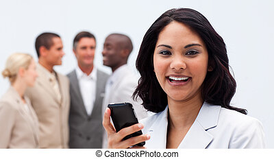 Smiling ethnic businesswoman texting with a mobile phone