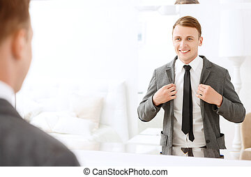 Smiling man holding jacket put on him - Feeling confident....