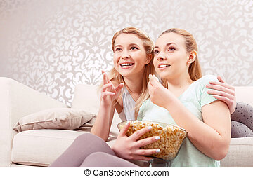 Young girls on a couch - Girls night in. Beautiful young...