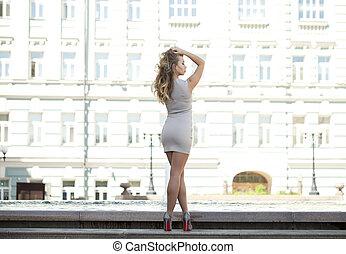 Young beautiful woman in beige short dress posing outdoors...