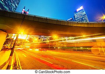 traffic light trails in modern business city under pedestrian bridge