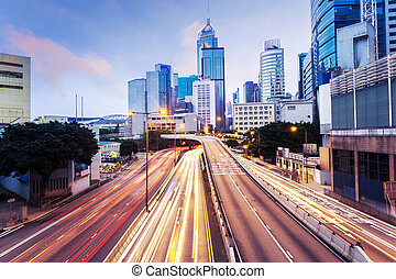 modern urban city traffic trails with cityscape background