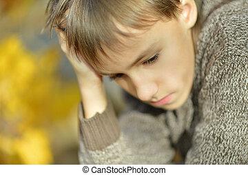 Little sad boy in autumn park close-up