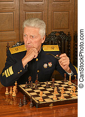Military mature general at the table playing chess