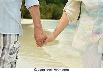 elderly couple walking along the seashore - happy elderly...