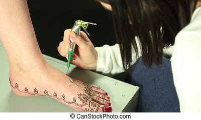 Master draws with henna on models leg - Mehndi art View of...