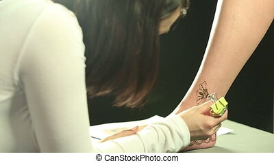View of master draws with henna on model's leg