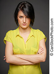 Confident woman staring deeply at you with her arms crossed