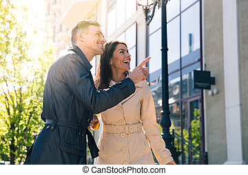Smiling man pointing on something to his wife