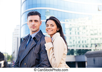 Portrait of a young smiling couple looking at camera -...