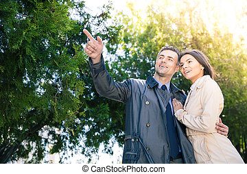 Smiling man pointing on something to his girlfriend