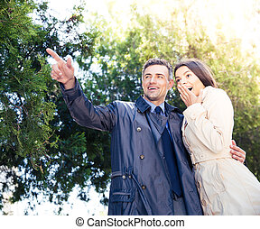 Man pointing on something with happy woman