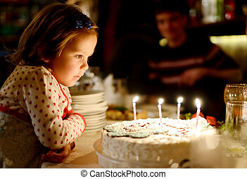 Little girl and birthday cake - Little girl blowing out...