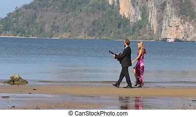 guitarist walks playing  girl follows dancing against cliffs