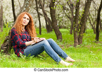 woman writer - beautiful red-haired woman writing in a...