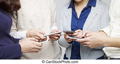 people using cellphone - small group of people using...
