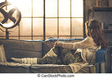 Woman in casual clothing sitting on sofa looking out - Seen...