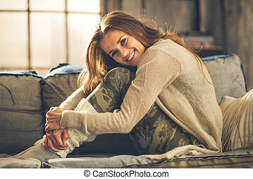 Smiling woman on sofa in loft, hugging her knees - An...
