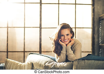 Brunette leaning over sofa smiling, resting chin on hands -...