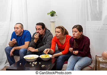 Exciting telecast - Four friends watching an exciting movie...