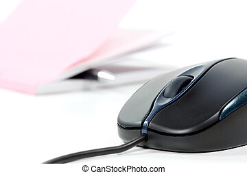 Black computer mouse and writing pad in background