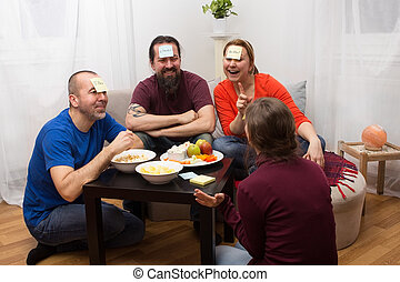 Funny guessing game - Friends sitting together and playing a...
