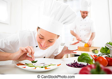 Young attractive professional chef cooking in his kitchen -...