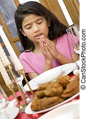 Girl praying during dinner