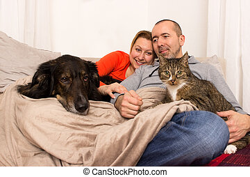 Together on a couch - A couple lying with her dog and her...