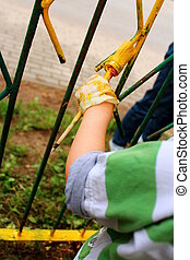 Spring cleaning in the garden - A child paints a fence brush...