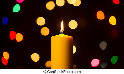 Burning Candle Against Holiday Lights Background