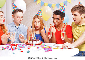 Young people celebrating a birthday sitting at the table